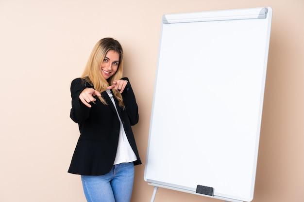Молодая уругвайская женщина дает представление на белой доске и указывает пальцем на вас