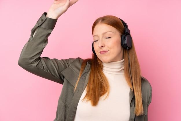 音楽を聴くと踊りの分離のピンクの壁の上の若い赤毛の女性