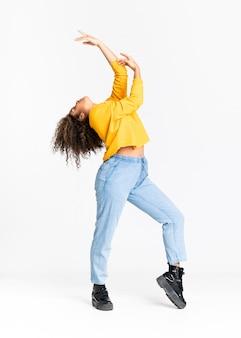 孤立した白い壁の上に踊る若い女性