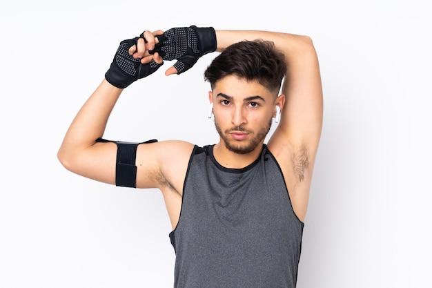 Человек спорта изолированный на белой стене протягивая руку