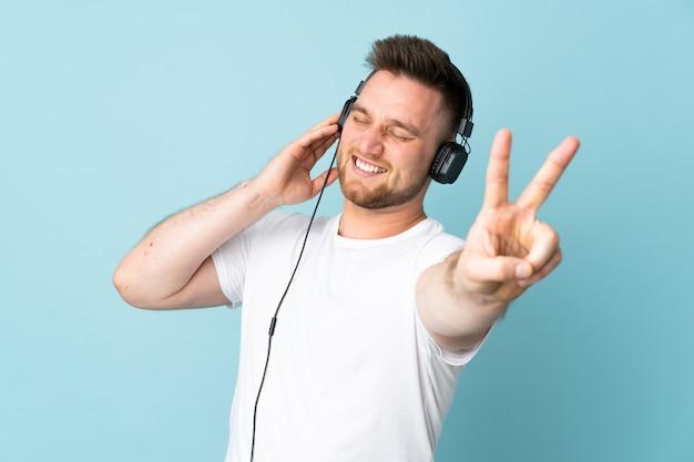 Красивый мужчина изолирован на синей стене прослушивания музыки и пения