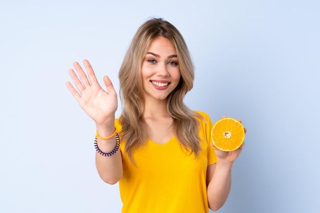 幸せな表情で手で敬礼青い壁に分離されたオレンジを保持しているティーンエイジャーの女の子