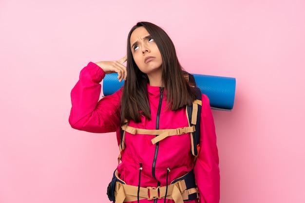 頭に指を置く狂気のジェスチャーを作る孤立したピンクの壁に大きなバックパックを持つ登山少女