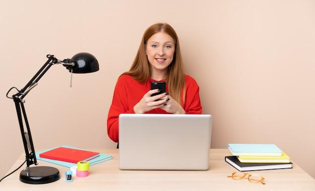 携帯電話でメッセージを送信するラップトップで職場の若い学生女性