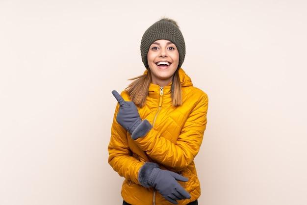 側に指を指している孤立した壁の上の冬の帽子を持つ女性