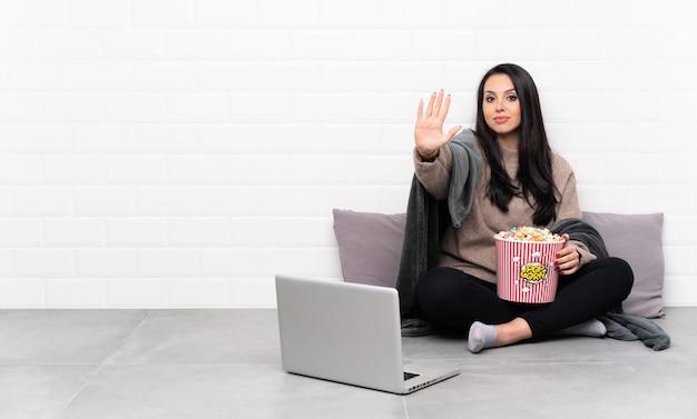 Молодая девушка, держа миску попкорна и показывая фильм в ноутбуке, делая жест остановки