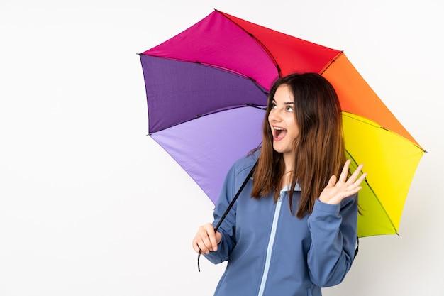 Женщина держит зонтик на белом с удивленным выражением лица