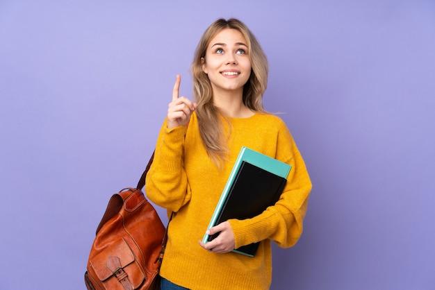 Девушка студента подростка на пурпуре указывая вверх и удивленная
