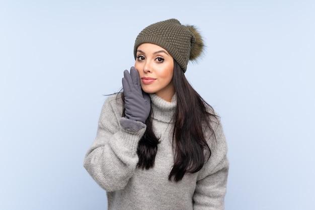 何かをささやく青い上の冬の帽子を持つ少女
