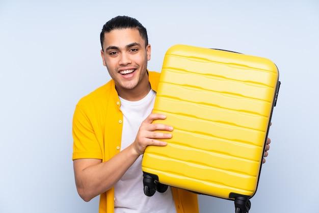 旅行スーツケースと休暇で青のハンサムな男と驚いた