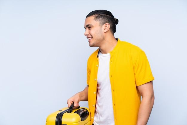 旅行スーツケースと休暇で青のハンサムな男