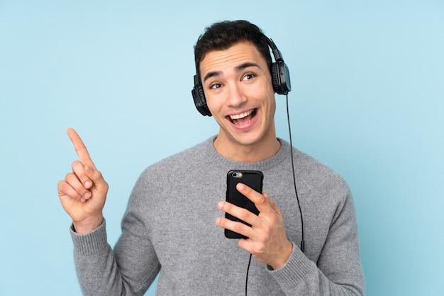 Молодой красавец на синем прослушивания музыки с мобильного телефона и пения