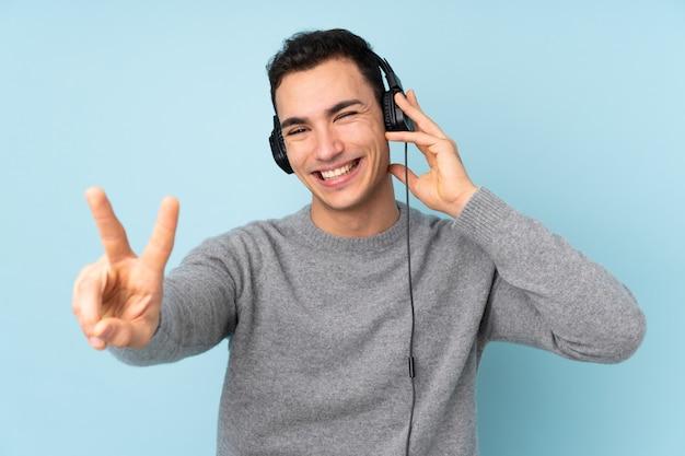 Молодой красавец на синем прослушивания музыки и пения