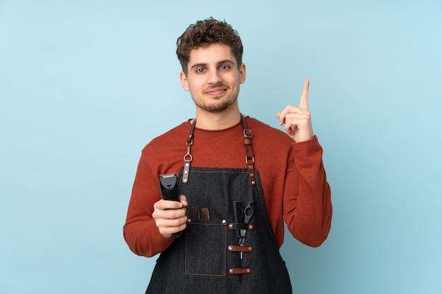 Парикмахер мужчина на синем, указывая указательным пальцем отличная идея