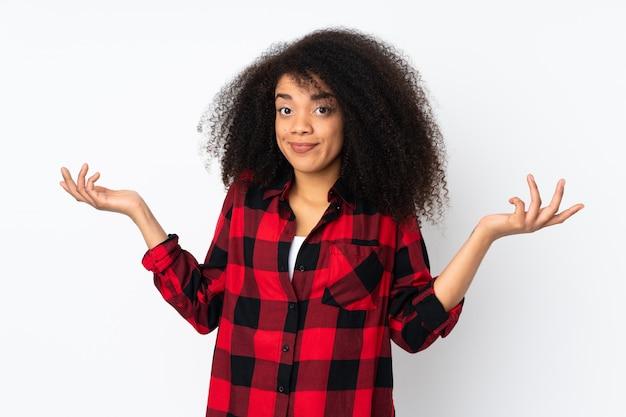 Молодая афро-американская женщина над стеной делая жест сомнения