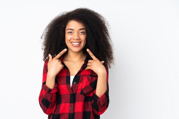 Молодая афро-американская женщина над стеной давая жест больших пальцев руки вверх
