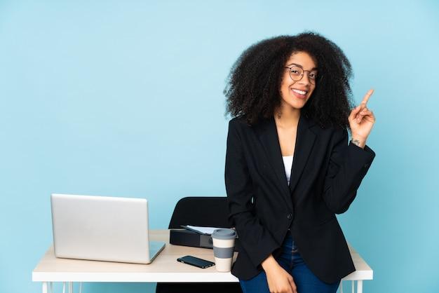 アフリカ系アメリカ人ビジネスの女性が彼女の職場で働くと指を持ち上げる