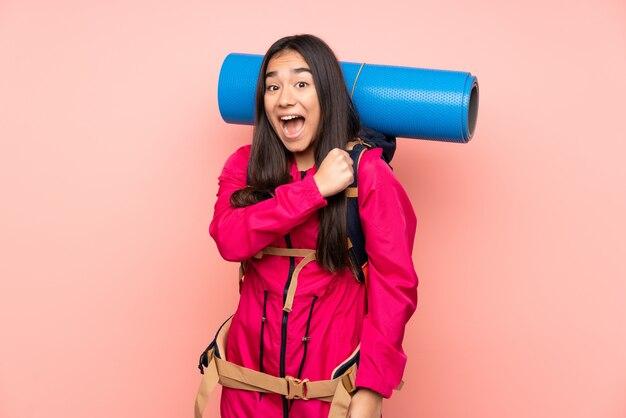 Молодой альпинист индийская девушка с большим рюкзаком на розовой стене празднует победу