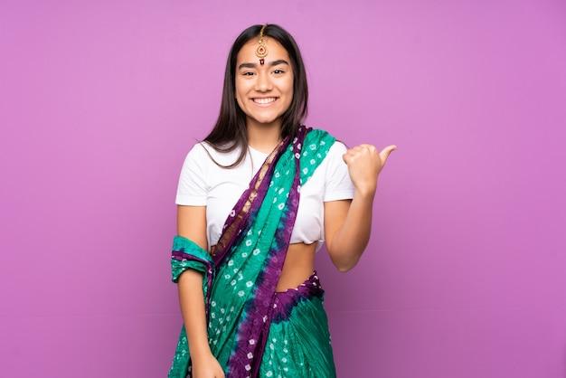 側を指している壁の上のサリーと若いインド人女性