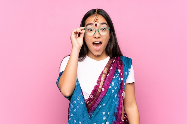 メガネと驚いた壁の上のサリーと若いインド人女性