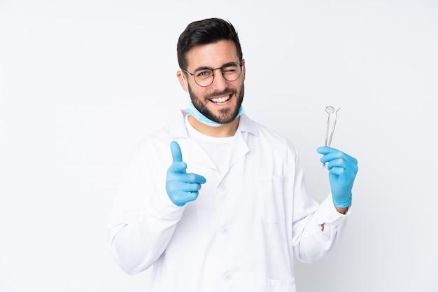 Стоматолог мужчина держит инструменты на белой стене указывает пальцем на вас