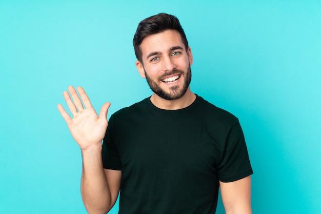 幸せな表情で手で敬礼青い壁に白人のハンサムな男