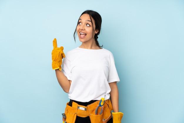 指を持ち上げながら解決策を実現しようとしている青い壁の若い電気技師の女性