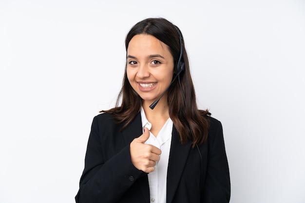 Молодая телемаркетер женщина на белой стене с недурно жест