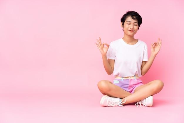 禅のポーズでピンクの壁の上の床に座って短い髪の若いベトナム人女性