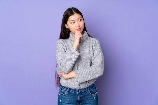 若いアジアの女性の壁と見上げる