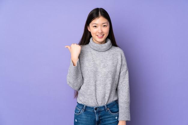 製品を提示する側を指している壁の上の若いアジア女性