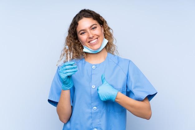 Молодая блондинка стоматолог, держа инструменты на голубой стене, давая пальцы вверх жест