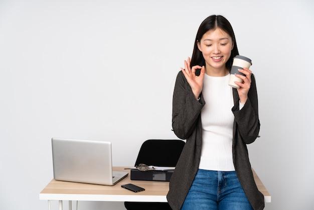 Бизнес азиатская женщина на своем рабочем месте на белой стене в позе дзэн