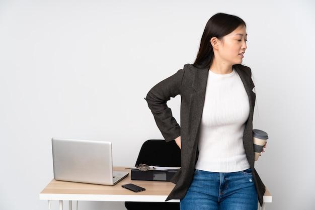 Женщина дела азиатская в ее рабочем месте на белой стене страдая от боли в спине для того чтобы сделать усилие