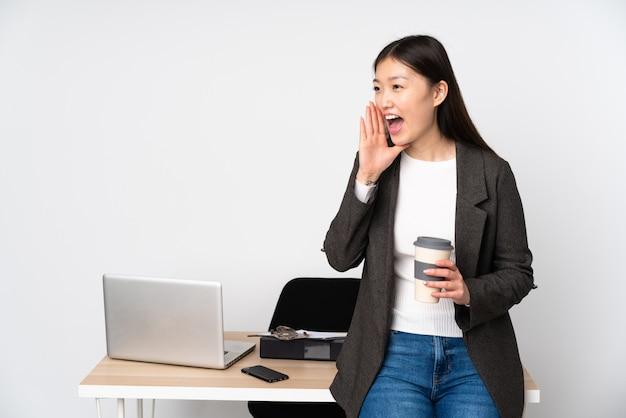 Бизнес азиатская женщина на своем рабочем месте на белой стене, крича с широко открытым ртом боковой