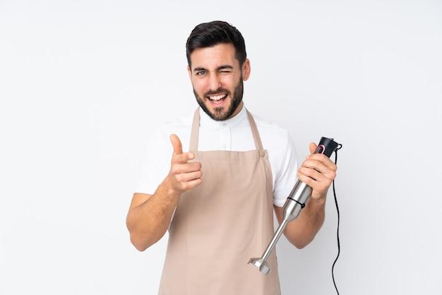 Человек, используя ручной блендер на белой стене указывает пальцем на вас