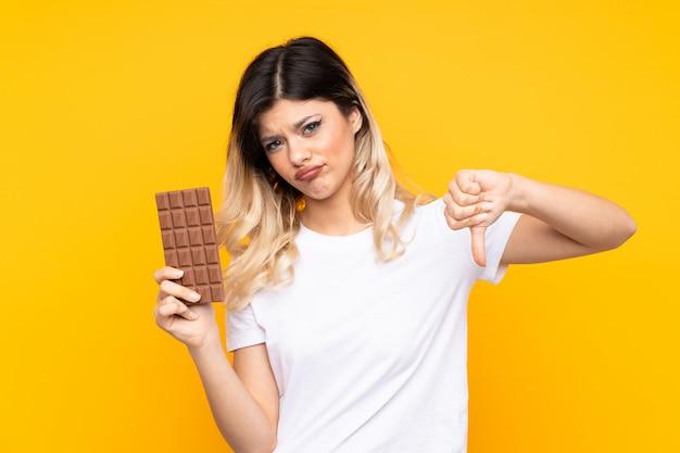 悪い信号を作るチョコレートタブレットを取って黄色の壁にティーンエイジャーの女の子