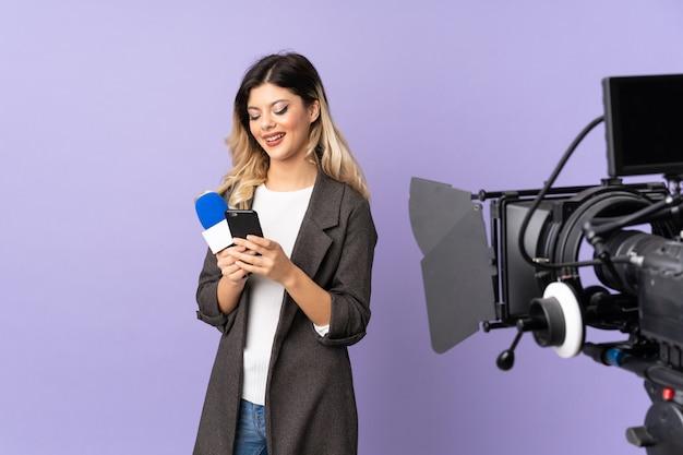 マイクを保持し、携帯電話でメッセージを送信する紫色の壁に関するニュースを報告するレポーターの女の子