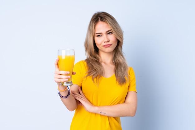 悲しそうな表情で青い壁にオレンジジュースを保持しているティーンエイジャーの女の子