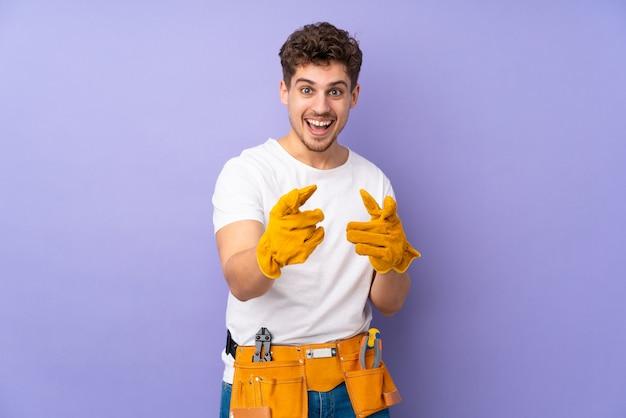 Молодой электрик человек на фиолетовой стене указывает пальцем на вас