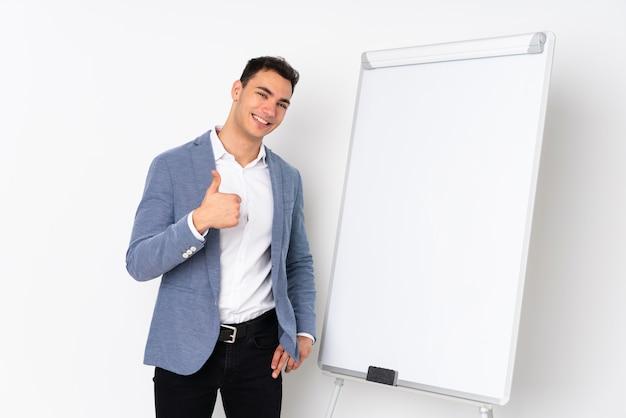 Молодой кавказской красавец на фиолетовые стены, презентации на белой доске и с большими пальцами руки вверх