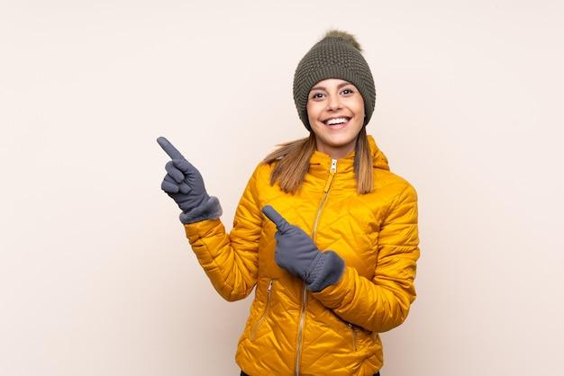 側に指を指す壁の上の冬の帽子を持つ女性