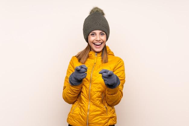 冬の帽子の壁の上の指を持つ女性