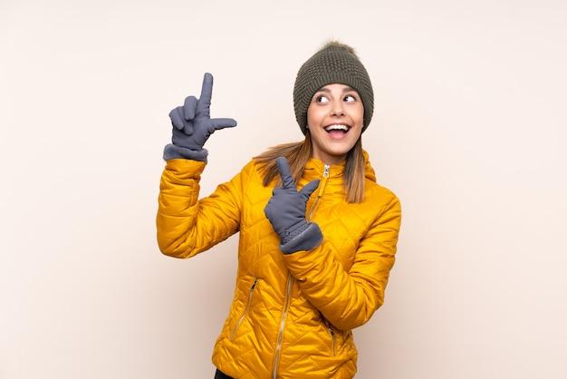 人差し指で素晴らしい壁を指している壁の上の冬の帽子を持つ女性