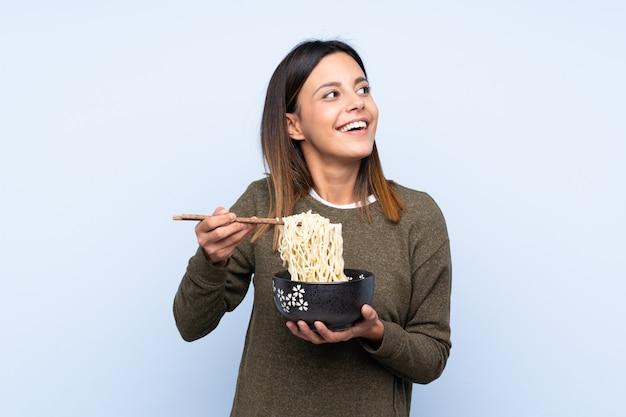 箸で麺のボウルを押しながら見上げる青い壁の上の女性
