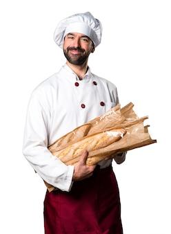 いくつかのパンを持っている幸せな若いパン屋
