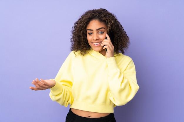 誰かと携帯電話で会話を続ける壁に若いアフリカ系アメリカ人女性