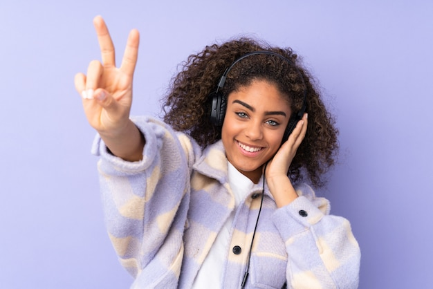 Молодая афро-американская женщина на фиолетовой стене слушая музыка и пея