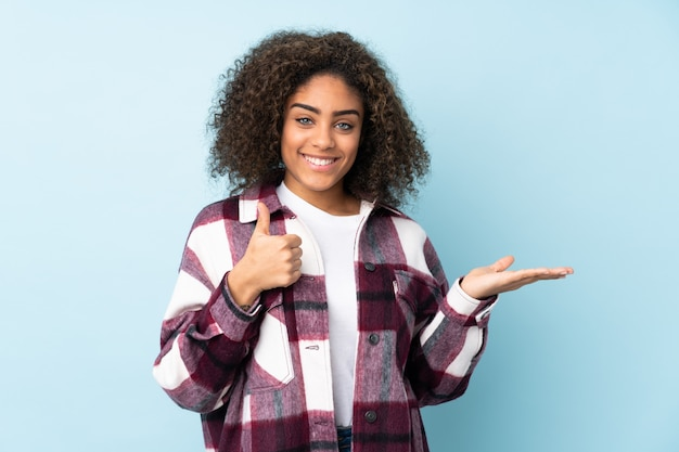 手のひらと親指で空白を保持している青い壁に若いアフリカ系アメリカ人女性