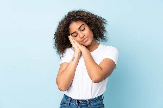 Молодая афро-американская женщина на голубой стене делая жест сна